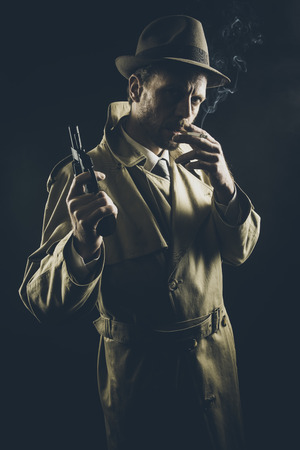 fedora hat: Film noir: attractive gangster in trench coat smoking a cigarette and holding a revolver