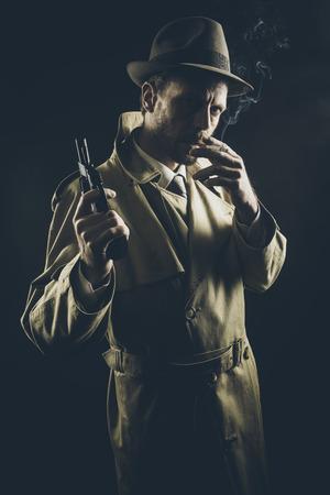 Film noir: Gángster atractivo en gabardina de fumar un cigarrillo y la celebración de un revólver