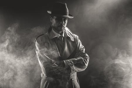Hombre misterioso esperando con los brazos cruzados en la niebla, 1950 estilo de cine negro Foto de archivo