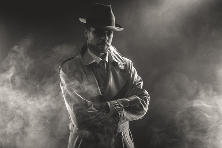 Mysterious man waiting with arms crossed in the fog, 1950s style film noir Stockfoto