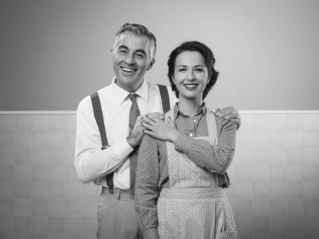 retro housewife: Happy vintage couple at home posing and smiling at camera
