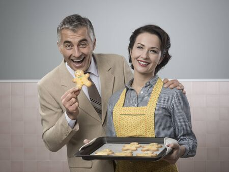 Vintage woman serving home made gingerbread men cookies to her smiling husband photo