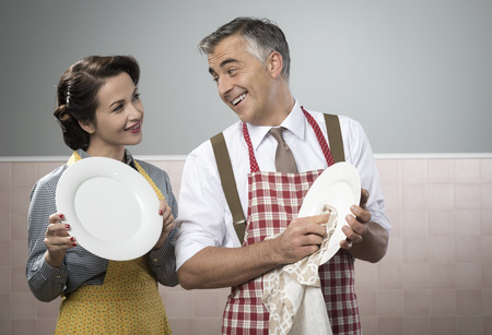Smiling vintage couple in apron dish washing together