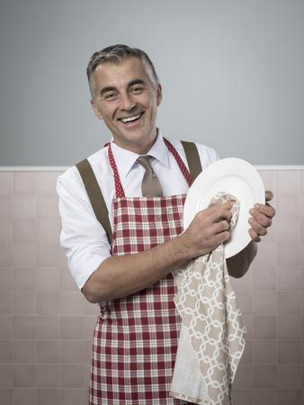 Hombre sonriente de la vendimia en el delantal de hacer las tareas domésticas platos de limpieza