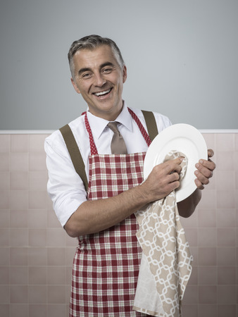 Vintage smiling man in apron doing household chores cleaning dishes