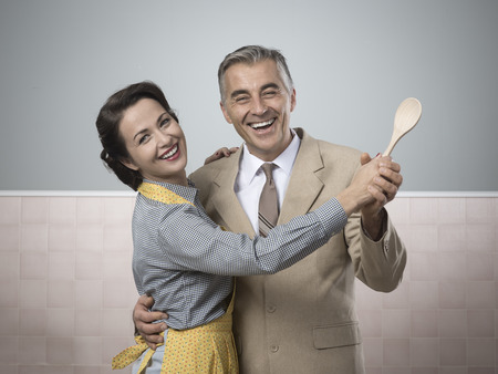 Smiling vintage couple dancing in the kitchen and holding a wooden spoon photo
