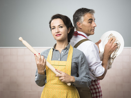 vintage power: Smiling strong woman with rolling pin watching her husband cleaning dishes