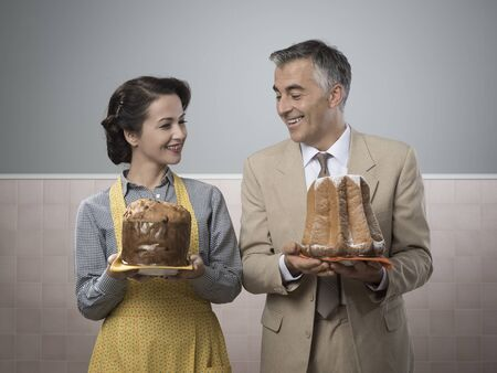 Smiling vintage couple staring at each others cake photo