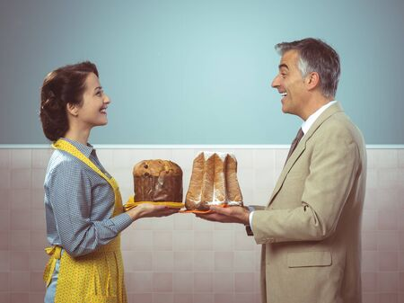 Smiling vintage couple with traditional italian cake panettone and pandoro photo