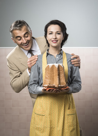 Smiling vintage couple with traditional italian pandoro photo