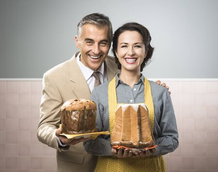 retro housewife: Smiling vintage couple with traditional italian cake panettone and pandoro