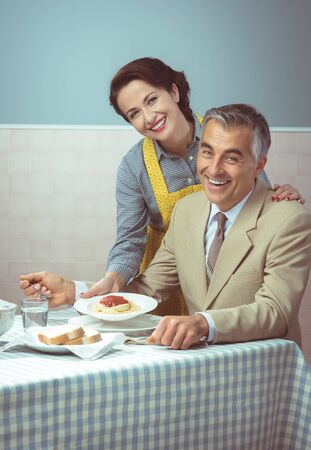 husband: Vintage smiling woman serving pasta for lunch to her happy husband Stock Photo