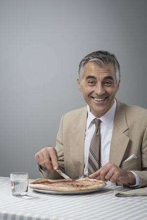 pause repas: Sourire d'affaires �l�gant ayant une pizza pendant sa pause d�jeuner