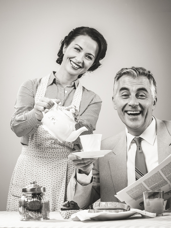 retro housewife: 1950s beautiful woman serving tea for breakfast to her smiling husband