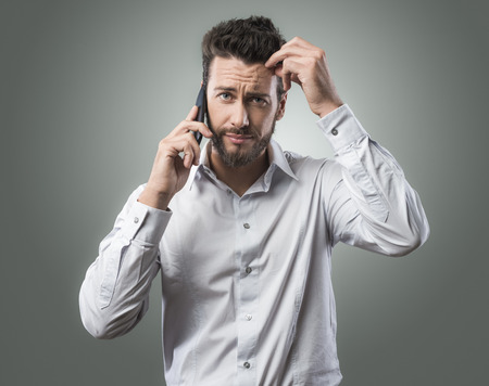 confuse: Disappointed confused young man on the phone having a call Stock Photo