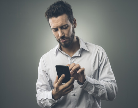 adult texting: Young confident man texting with his mobile phone