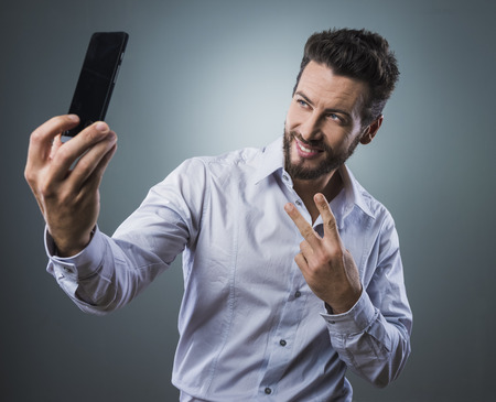 photo shooting: Cool handsome man taking self portraits with his smartphone Stock Photo