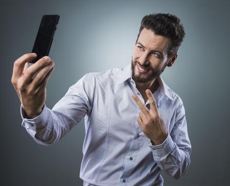 hombre disparando: Fresco hermoso hombre tomar autorretratos con su teléfono inteligente