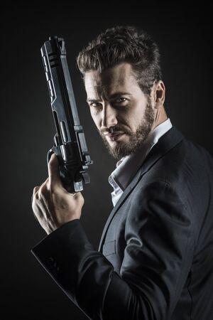 暗い背景に危険な武器を保持している勇敢なクールな男 写真素材