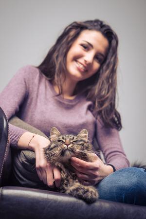 amigos abrazandose: Mujer sonriente joven que abraza a su gato hermoso pelo largo