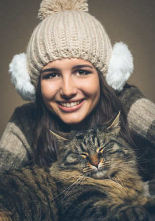 ear muffs: Beautiful woman with hat and ear muffs and cat smiling at camera Stock Photo