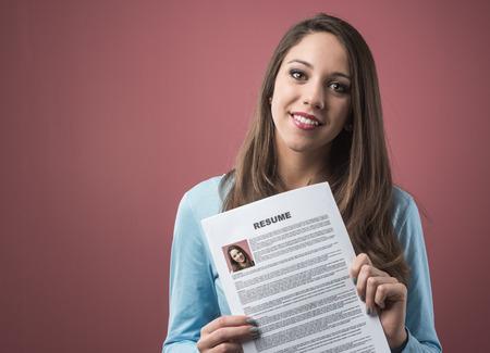 competencias laborales: Joven mujer sonriente sosteniendo su curriculum vitae y solicitar un empleo