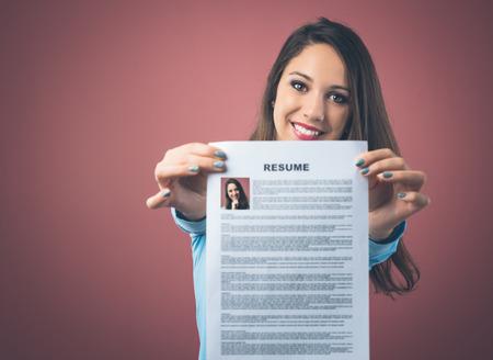 cv: Joven mujer sonriente sosteniendo su curriculum vitae y solicitar un empleo