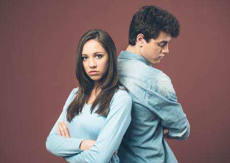 emotional stress: Young sad couple arguing and standing back to back Stock Photo