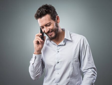 on call: Smiling young businessman having a phone call with his mobile