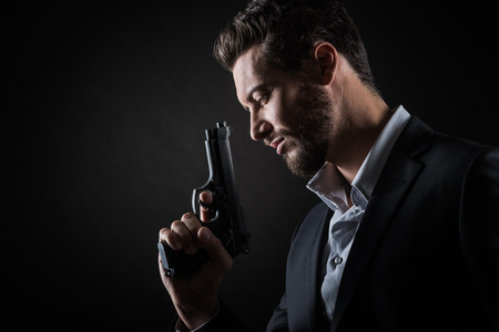 man profile: Brave cool man holding a gun on dark background Stock Photo