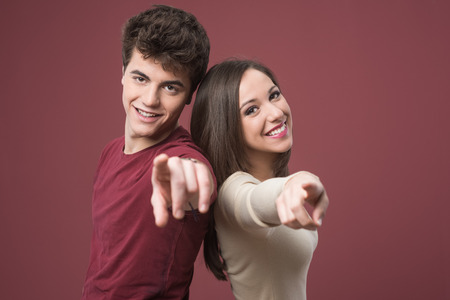 Happy young couple pointing at camera and smiling on red background photo