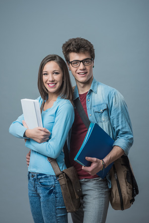 Cheerful smiling students with textbooks hanging out together