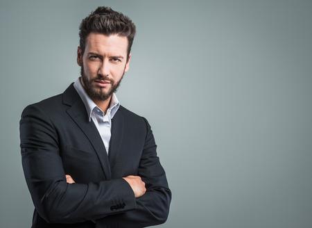 confianza: Hombre de negocios joven confidente que presenta sobre fondo gris