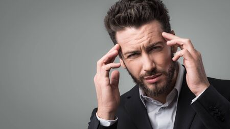 frowning: Sad businessman head in hands frowning with headache