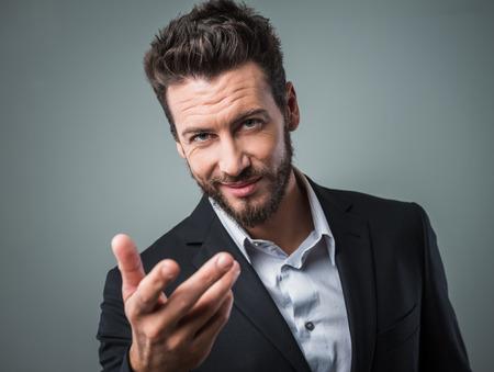 invitando: Atractivo flirteo hombre e invitando a alguien con la mano abierta