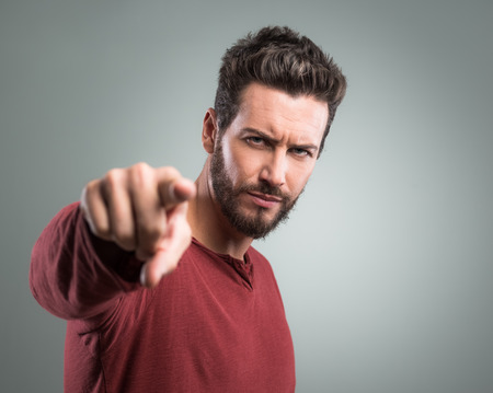 provocation: Angry attractive young man pointing at camera on gray background