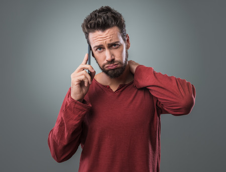 puffing: Young man having a boring phone call snorting and frowning