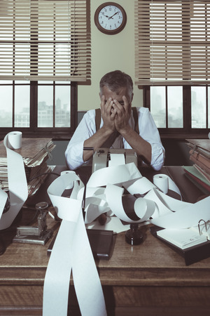 overburdened: Desperate accountant head in hands surrounded by bills on paper tape, 1950s style office.