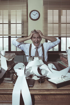 overburdened: Desperate accountant shouting head in hands in vintage 1950s style office. Stock Photo