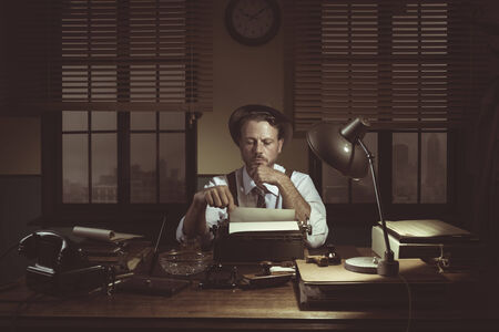 Confident journalist checking errors on text working at his desk, 1950s style office.