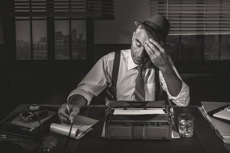 Periodista profesional que trabaja a altas horas de la noche en su escritorio con máquina de escribir vintage, estilo de 1950. Foto de archivo