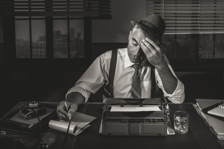Professional reporter working late at night at his desk with vintage typewriter, 1950s style. Reklamní fotografie - 36414972