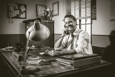 cheesy grin: Smiling director working at desk having a phone call, 1950s style office.