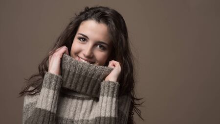 sweater girl: Attractive young woman with high collar sweater smiling at camera