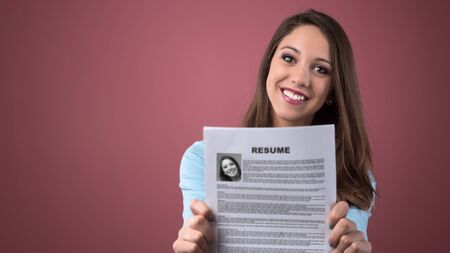 business interview: Young smiling woman holding her resume and applying for a job