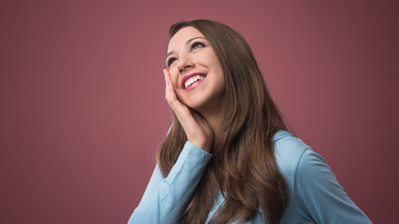 cheek: Young beautiful smiling woman daydreaming with hand on cheek Stock Photo