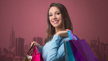 gift spending: Smiling happy woman shopping with lots of colorful bags