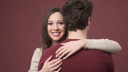 affinity: Happy young woman hugging her boyfriend on red background