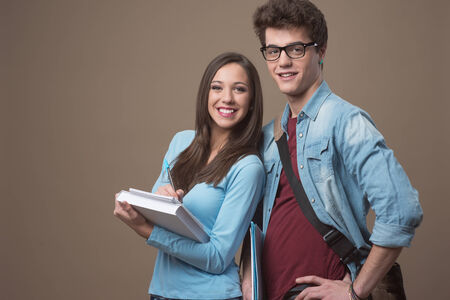 textbooks: Happy teenager students holding textbooks and smiling Stock Photo