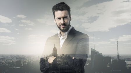 man's suit: Confident young businessman posing with cityscape on background